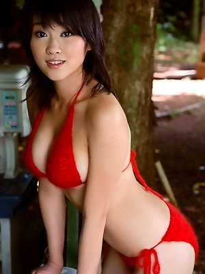 Voluptuous asian chick shows off her big boobs in a little bikini